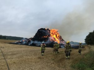 pile of straw on fire with firefighters in the foreground